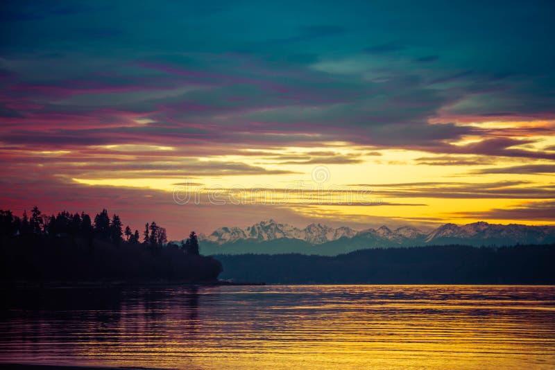 Briljante Zonsondergang over het Vreedzame Noordwesten met Evergreens in Silhouet met Gele en Blauwe Tonen stock fotografie