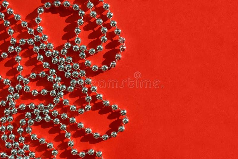 Briljanten försilvrar den kulöra pärljulgirlanden på texturerad röd bakgrund under det ljusa solskenet, den festliga lägenheten l royaltyfri foto