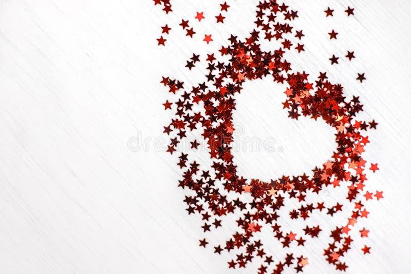 Brilla el corazón rojo de las pequeñas estrellas de la chispa imagen de archivo