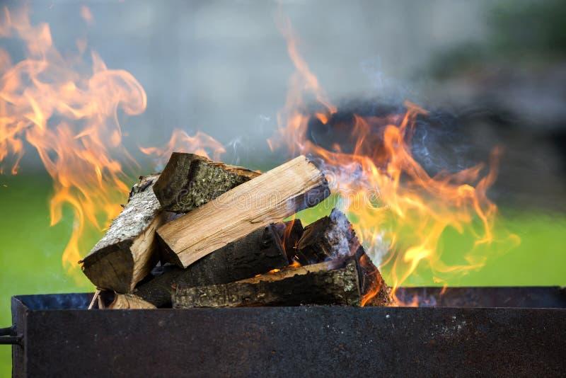Brillamment brûlant en bois de chauffage de boîte en métal pour le barbecue extérieur Concept de camping, de sécurité et de touri images stock