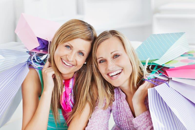 Brillando intensamente dos mujeres que celebran la sonrisa de los bolsos de compras fotos de archivo libres de regalías