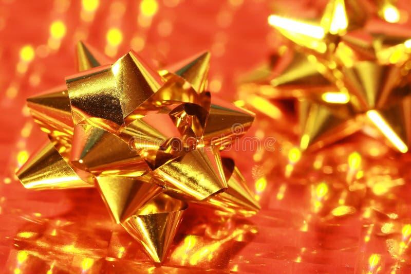 Or brillant de proue de cadeau sur l'or photos stock