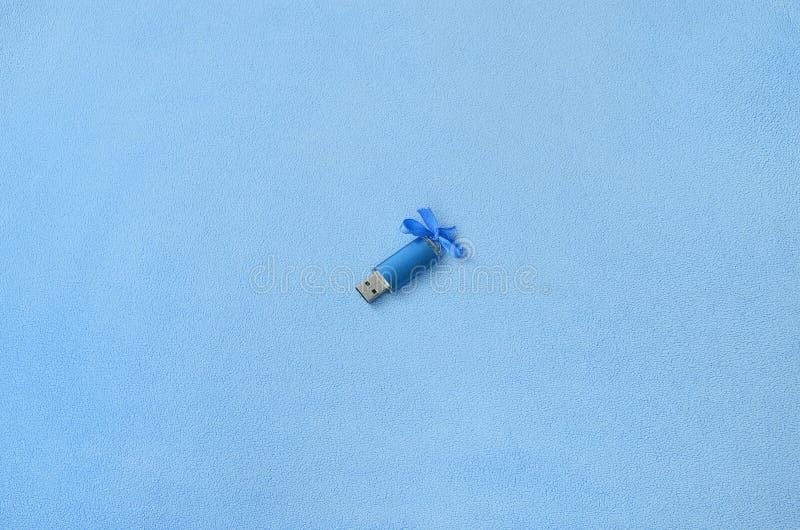 Brillantblau usb-Flash-Speicher-codierte Karte mit einem blauen Bogen liegt auf einer Decke des weichen und pelzartigen hellblaue stockbild