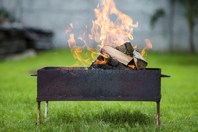 Brillantemente bruciando in legna da ardere del contenitore di metallo per il barbecue all'aperto Concetto di campeggio, di sicur immagine stock