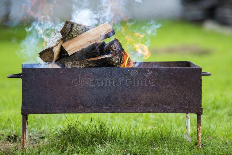 Brillantemente quemando en la leña de la caja del metal para la barbacoa al aire libre leva imagenes de archivo