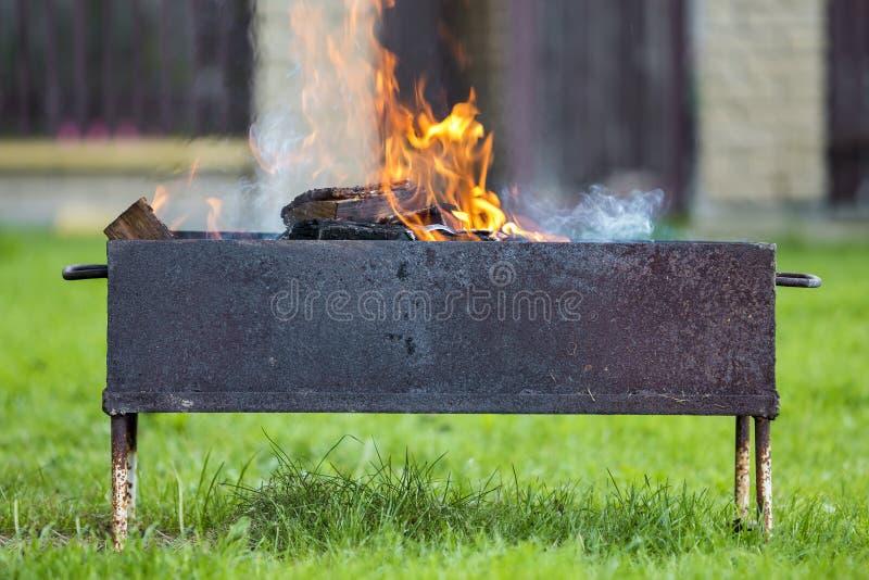Brillantemente quemando en la leña de la caja del metal para la barbacoa al aire libre leva imagen de archivo libre de regalías