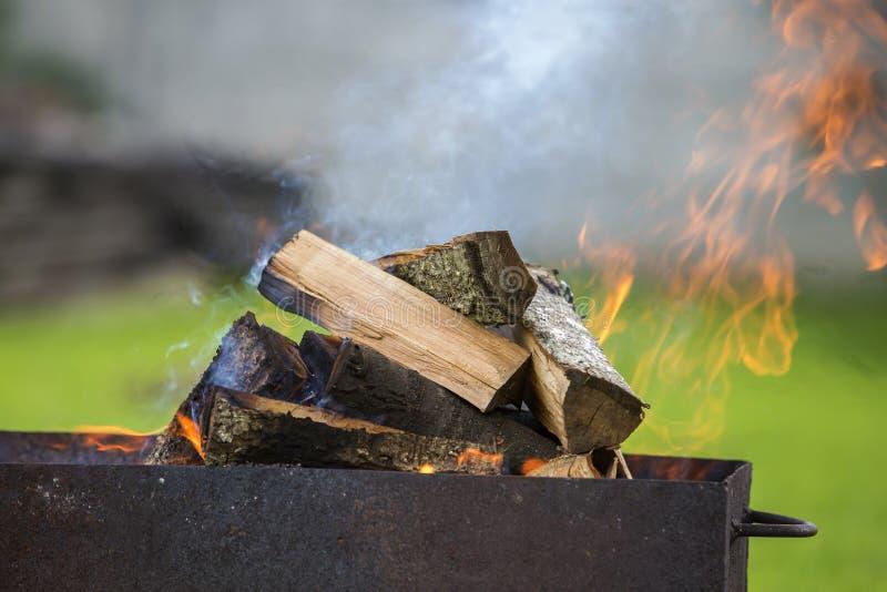 Brillantemente quemando en la leña de la caja del metal para la barbacoa al aire libre leva foto de archivo libre de regalías