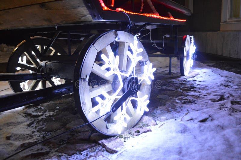 Brillar intensamente las ruedas, guirnalda de la Navidad bajo la forma de copos de nieve en el carro de madera rueda fotografía de archivo libre de regalías