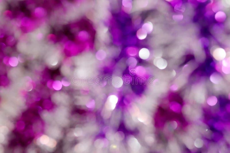 Brillare variopinto del bokeh porpora e rosa dell'immagine vaga per il Buon Natale e la progettazione del fondo di festival del b fotografia stock
