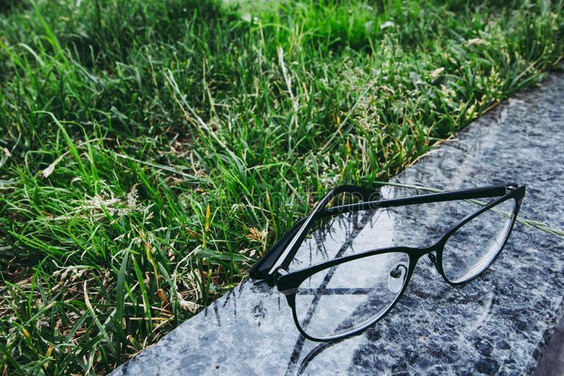 Brillen in der schwarzen Kante, die auf der Granitoberfläche nahe dem Gras liying ist stockbilder