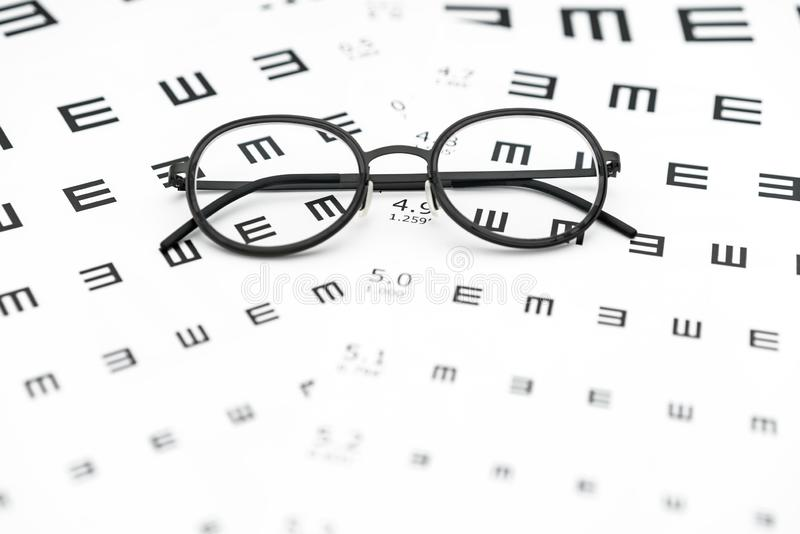 Brillen und Sehschärfediagramm im weißen Hintergrund stockbilder