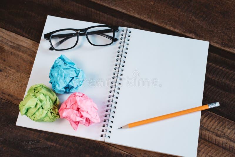 Brillen, zerknittertes Papier und leeres gewundenes Notizbuch mit Kopienraum auf einem Holztisch lizenzfreies stockbild