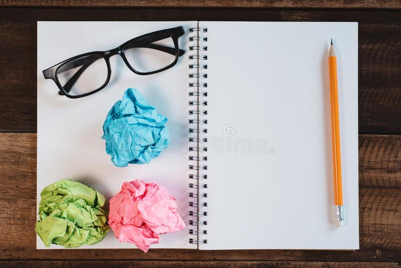 Brillen, zerknittertes Papier und leeres gewundenes Notizbuch mit Kopienraum auf einem Holztisch lizenzfreie stockbilder