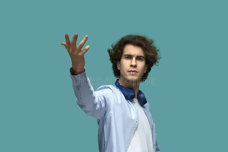 Brilliant creator. Portrait of serious young beautiful man wearing white t-shirt and blue shirt in headphones raised his hand for. Calling and looking at camera royalty free stock image