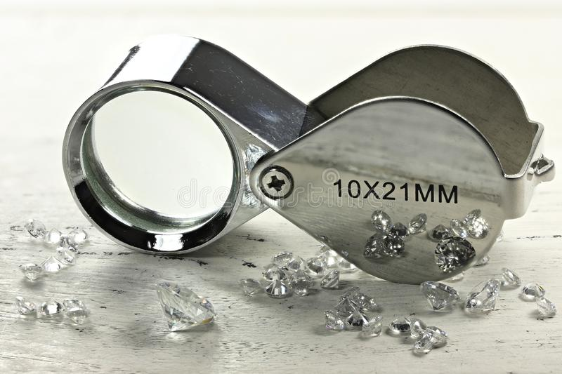 Diamonds. Brilliant cut diamonds with folding magnifier on wooden background royalty free stock photos