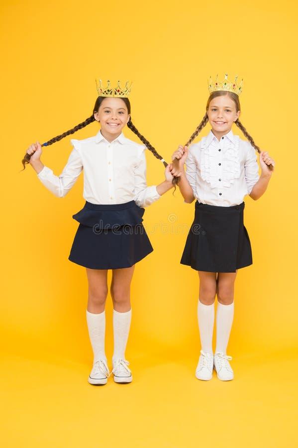 Brilliant pupils. Schoolgirls wear golden crowns symbol of respect. Award and respect. Cute princess. Motivational award. For school children. Girls kids royalty free stock photo
