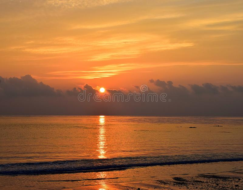 Brilliant Shining Yellow Sun Rising at Horizon over Ocean with Golden Reflection in Water and Bright Yellow Warm Colors in Sky royalty free stock image