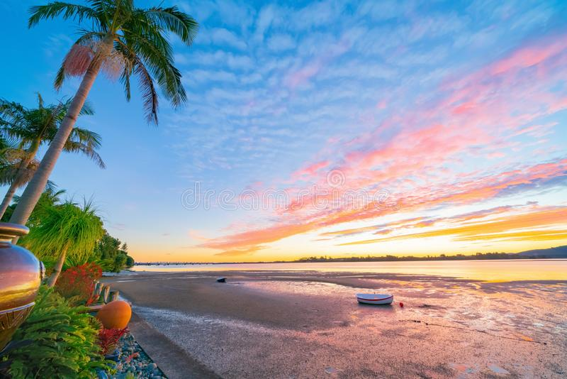 Brilliant sunset on harbor edge. With striking cloud formations over tropical gardens and beach at low tide Tauranga New Zealand royalty free stock photography