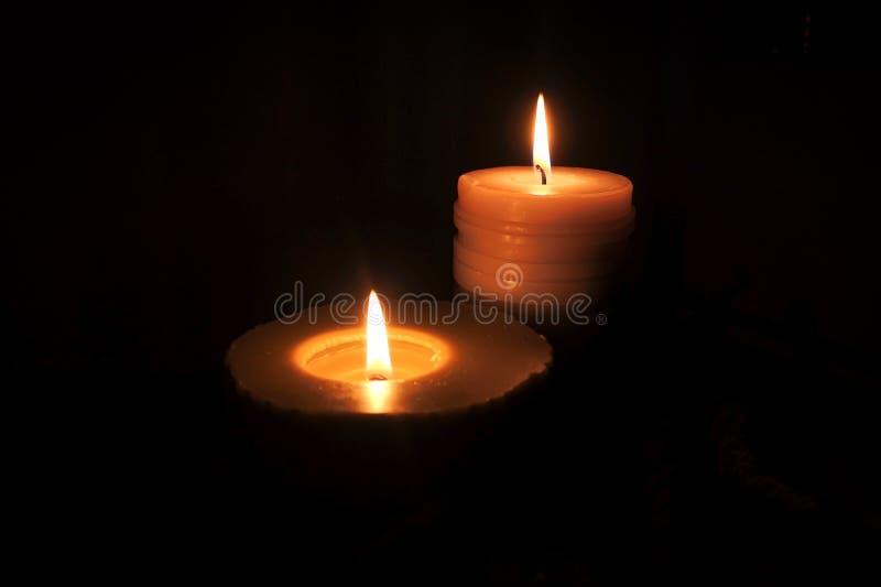 Brillo de la llama de vela en la oscuridad foto de archivo