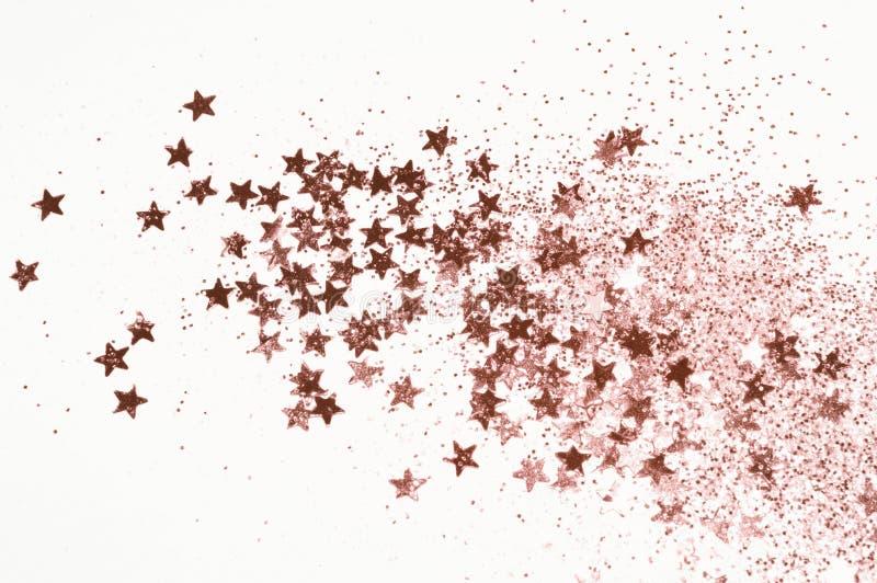 Brillo del oro de Rose y estrellas que brillan en fondo gris claro imagenes de archivo