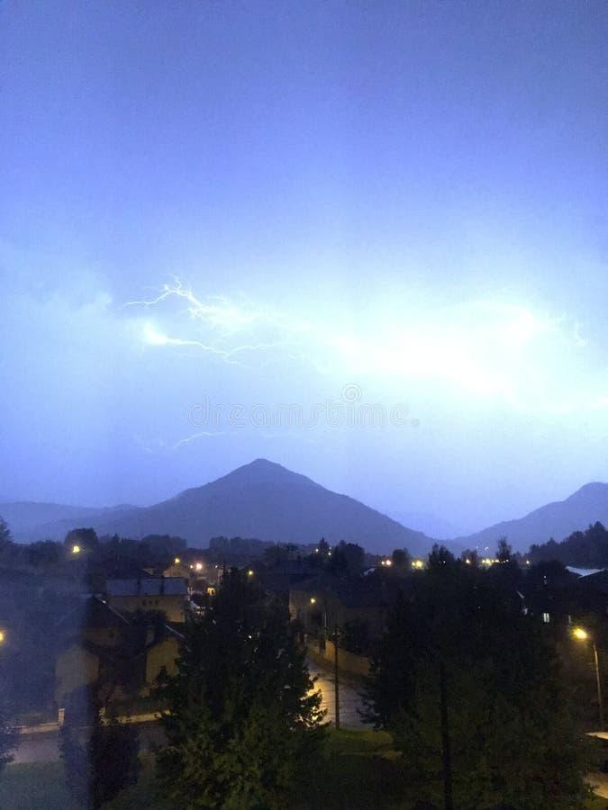 Brillo y tempestad de truenos sobre la montaña y la ciudad imagenes de archivo