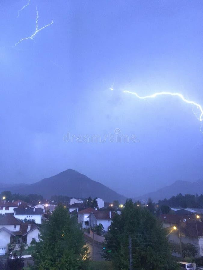 Brillo y tempestad de truenos sobre la montaña y la ciudad foto de archivo