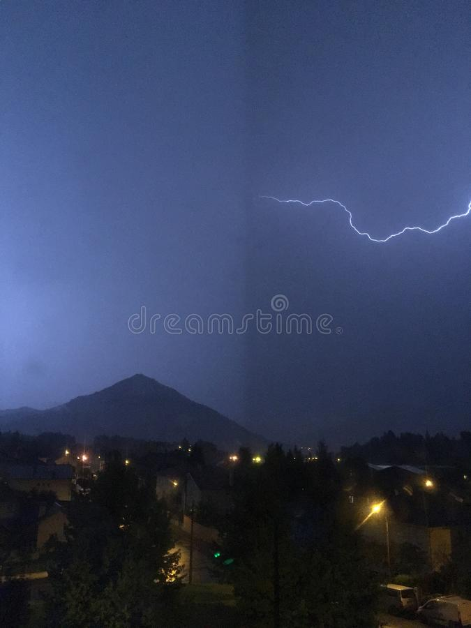 Brillo y tempestad de truenos sobre la montaña y la ciudad foto de archivo libre de regalías