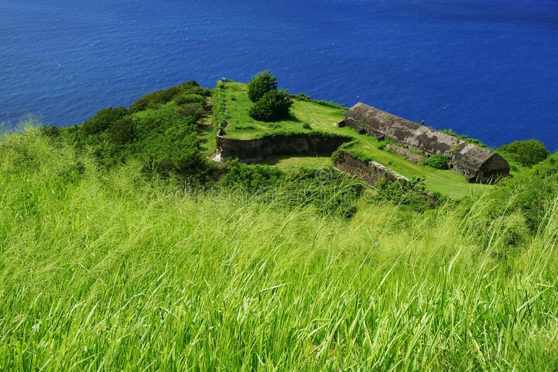 Brimstone Hill Fortress fortifications and buildings with green grass and bright blue sea. Brimstone Hill Fortress fortifications and buildings with klish green royalty free stock photography