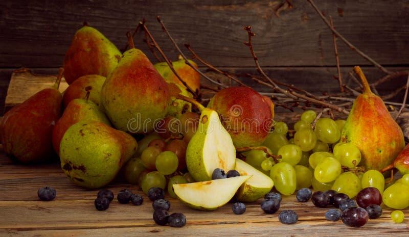 Brin des raisins et d'une poire délicieuse sur le fond en bois images libres de droits