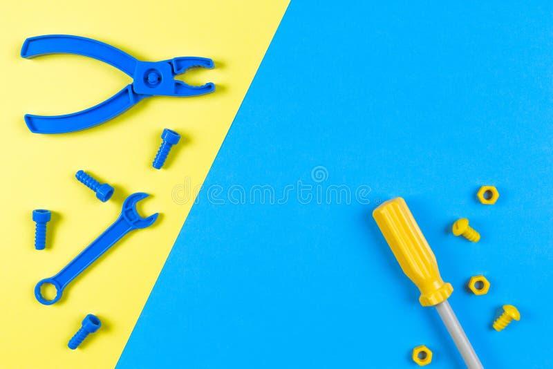 Brinca o fundo A construção das crianças brinca ferramentas no fundo azul e amarelo Vista superior fotografia de stock royalty free