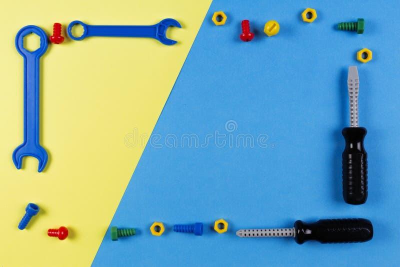 Brinca o fundo A construção das crianças brinca o quadro das ferramentas no fundo azul e amarelo Vista superior fotografia de stock royalty free