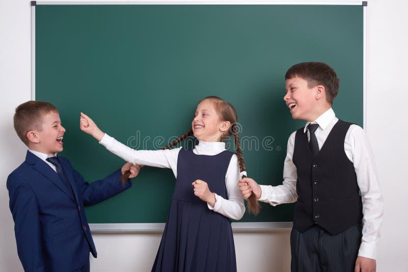 A brincadeira e o divertimento ter, meninos puxam as tranças da menina, perto do fundo vazio do quadro da escola, vestido no tern imagem de stock