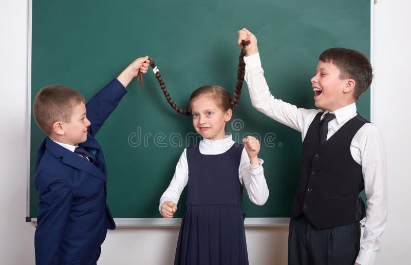 A brincadeira e o divertimento ter, meninos puxam as tranças da menina, perto do fundo vazio do quadro da escola, vestido no tern foto de stock