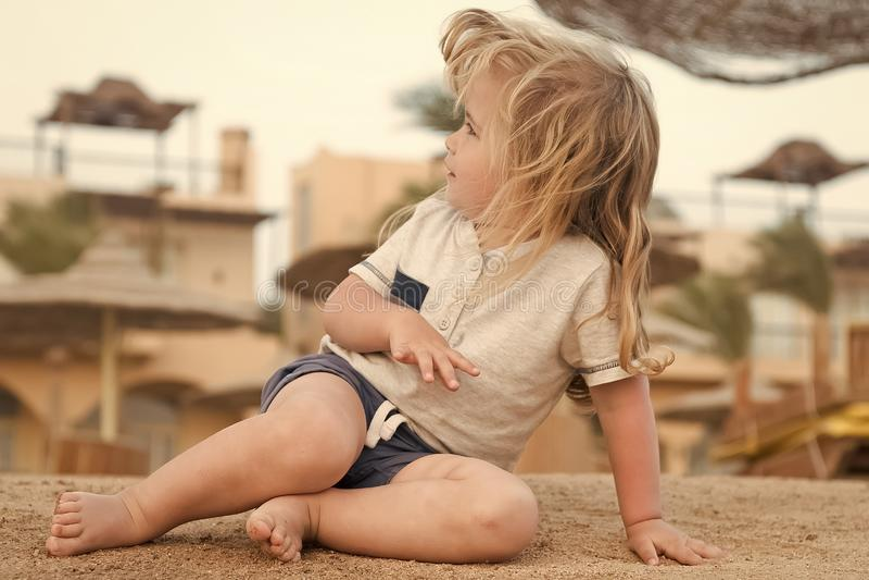 Brincadeira na areia O menino pequeno senta-se na praia tropical Atividade do verão na praia As férias, lazer e relaxam o conceit fotografia de stock royalty free