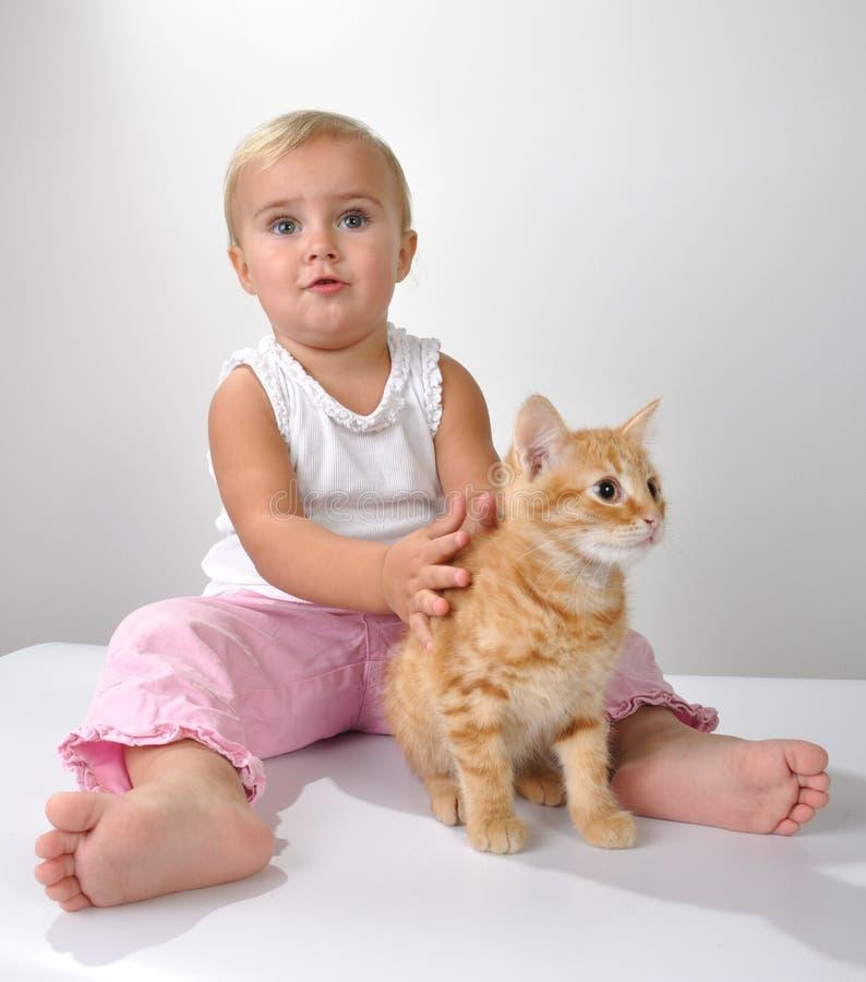 Brincadeiras da criança com um gato imagens de stock