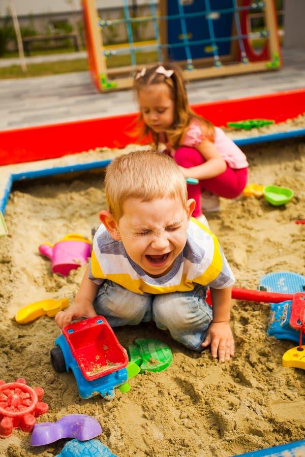 Brincando de garoto infeliz brincando com carro em caixa de areia imagens de stock royalty free