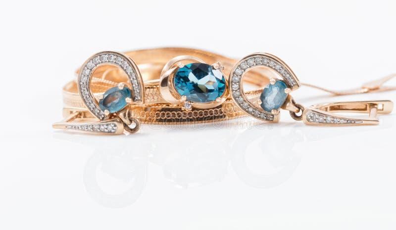 Brincos do ouro na forma em ferradura e de uns wi delicados de um anel imagem de stock