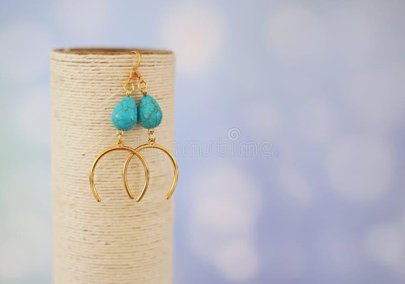 Brincos dourados com as pedras semi preciosas afortunadas da ferradura e da turquesa fotografia de stock