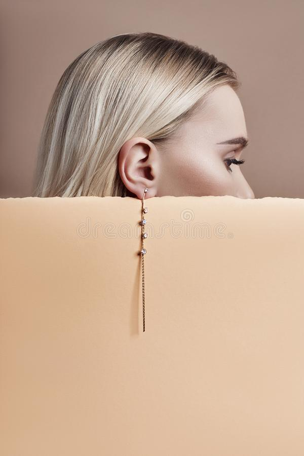 Brincos e joia na orelha de uma mulher loura 'sexy' pressionada contra o bege de papel Menina loura perfeita, olhar misterioso li imagem de stock