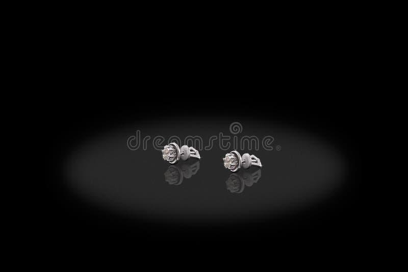 Brincos preciosos da platina com os diamantes grandes no fundo preto imagem de stock