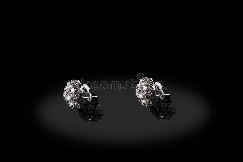 Brincos preciosos da platina com os diamantes grandes no fundo preto fotos de stock royalty free
