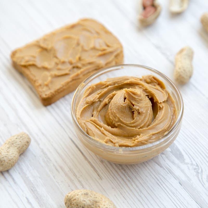 Brinde, bacia de manteiga de amendoim e amendoins nos shell em uma tabela de madeira branca, vista lateral imagens de stock royalty free
