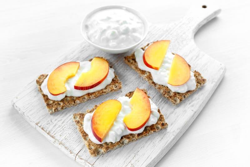 Brinde caseiro do pão estaladiço com requeijão e nectarina na placa de madeira branca fotografia de stock