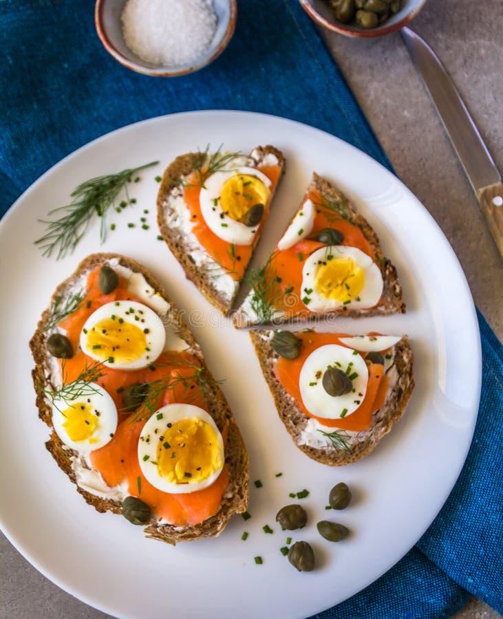 Brinde delicioso do sourdough do salmão fumado com o queijo creme da cabra e o ovo cozido do corte, decorados com aneto, cebolinh fotografia de stock