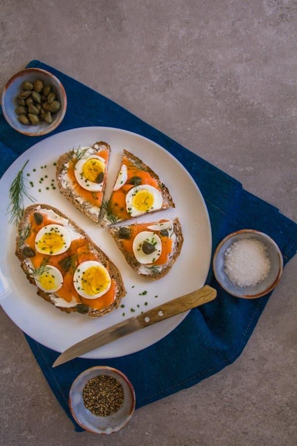 Brinde delicioso do sourdough do salmão fumado com o queijo creme da cabra e o ovo cozido do corte, decorados com aneto, cebolinh fotos de stock