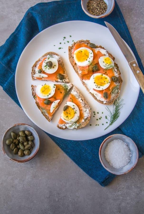 Brinde delicioso do sourdough do salmão fumado com o queijo creme da cabra e o ovo cozido do corte, decorados com aneto, cebolinh imagens de stock