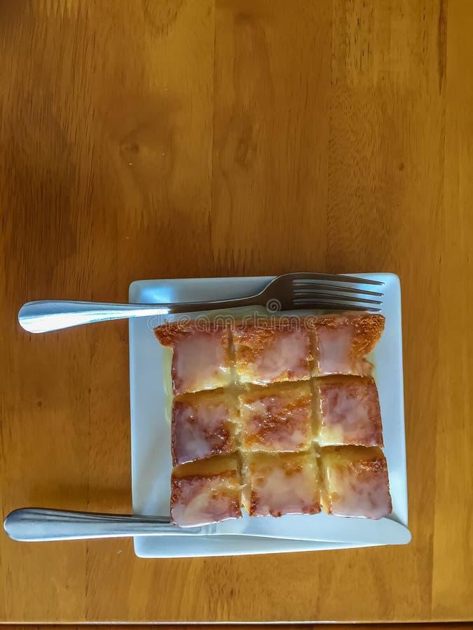 Brinde do mel no prato branco e colher, forquilha na tabela de madeira fotografia de stock royalty free