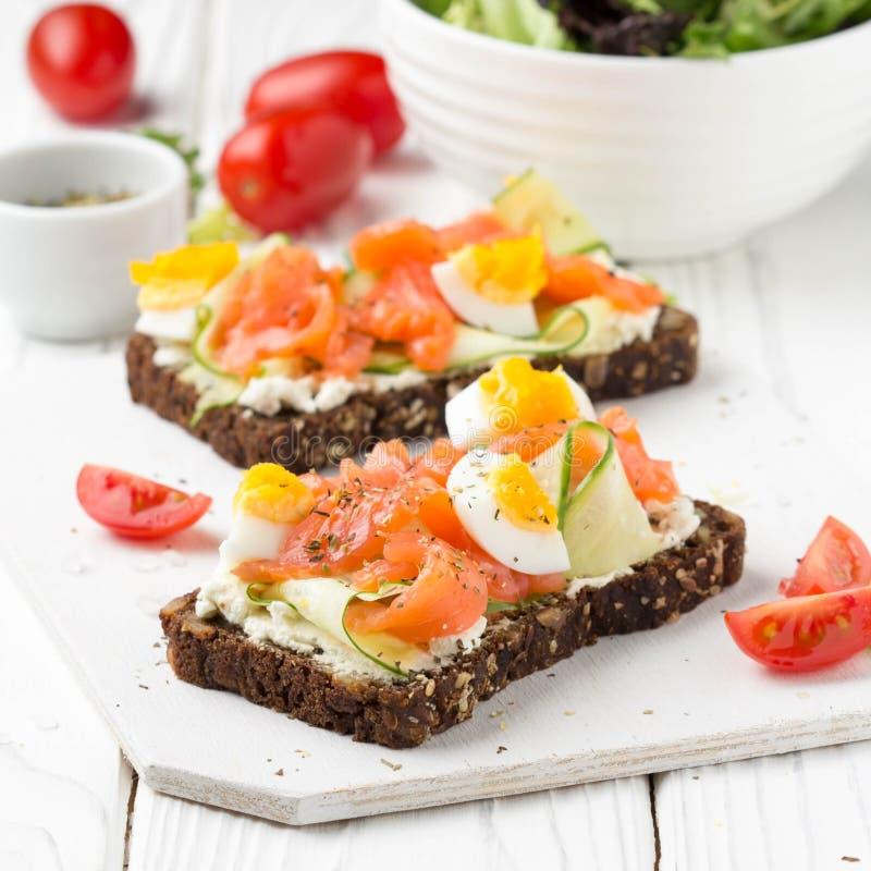 Brinde dos salmões com queijo creme, pepino e ovo Almoço delicioso, alimento saudável, sanduíche dos peixes, petisco da dieta imagens de stock royalty free