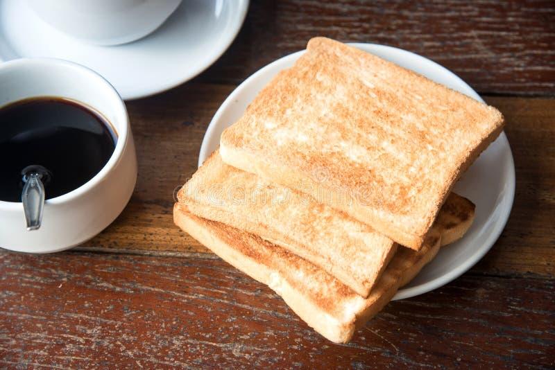 Brinde e café na tabela de madeira imagem de stock