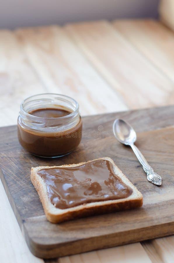 Brinde e frasco com manteiga de amendoim em uma placa de madeira fotografia de stock